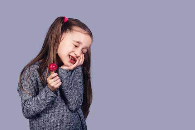 Kleines trauriges mädchen mit einem roten lutscher in ihren händen, dessen zähne schmerzten. das konzept der kariesentwicklung aufgrund des missbrauchs von süßigkeiten. isoliert auf grauer oberfläche