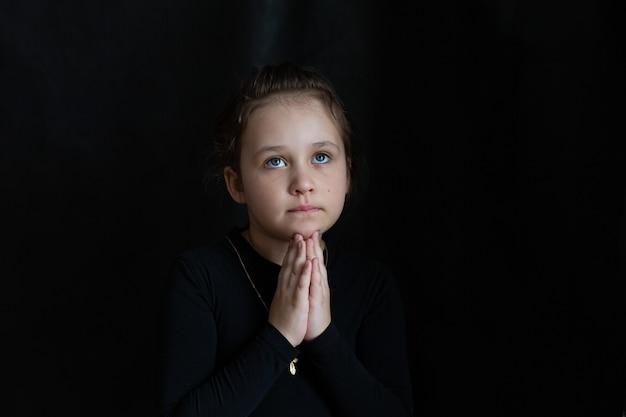 Kleines trauriges schrei-mädchen betet in schwarzen kleidern