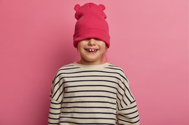 Kleines ungezogenes mädchen versteckt augen mit stilvollem hut, hat spaß und will nicht zum kindergarten gehen, hat zahniges lächeln, ist in bester fröhlicher stimmung, posiert über pastellrosa wand. kinder, mode, stil