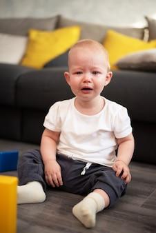 Kleines unglückliches kind, das auf dem boden in seinem zimmer weint