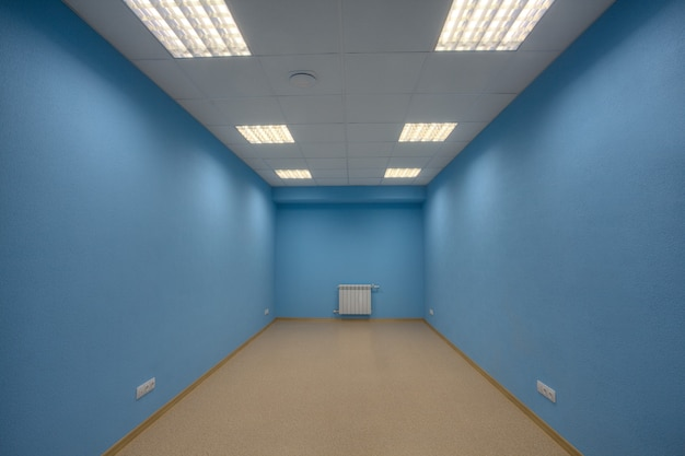 Kleines verlassenes unmöbliertes büro, keine karosserie und keine fenster, die wände sind blau gestrichen.