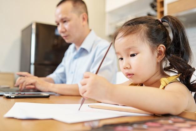 Kleines vietnamesisches mädchen, das das zeichnen mit bleistift genießt, wenn es am tisch neben ihrem vater sitzt, der mit der arbeit am laptop beschäftigt ist