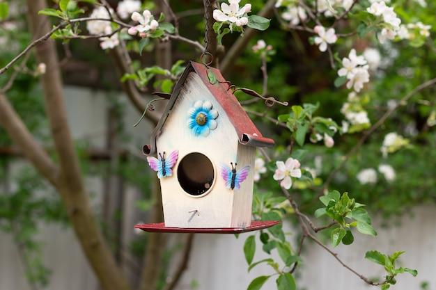 Kleines vogelhaus im frühjahr über einem blühenden apfelbaum. frühlingszeit natur