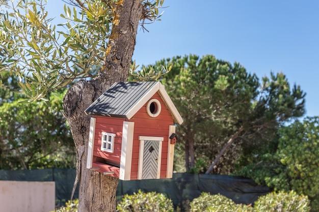 Kleines vogelhaus über holztisch draußen im garten