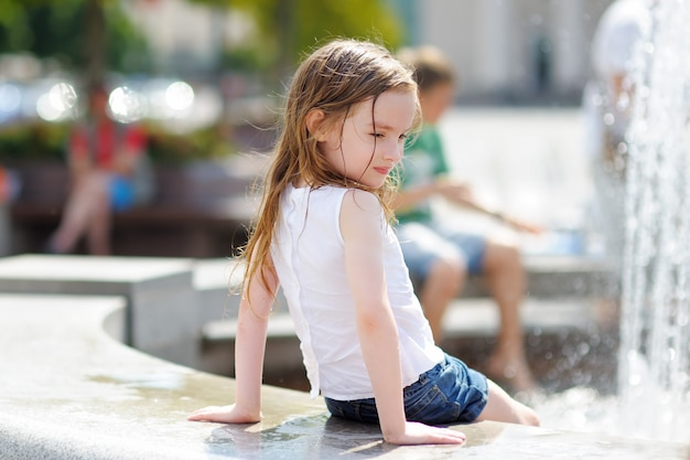 Kleines vorschülermädchen, das mit einem stadtbrunnen am sommertag spielt