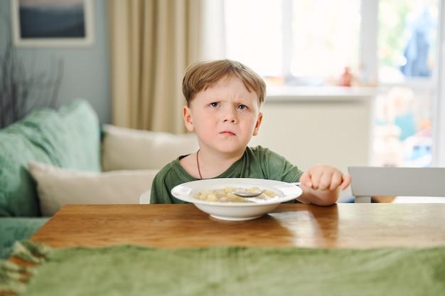 Kleines vorschulkind, das suppe auf der küche isst und auf dem tisch sitzt