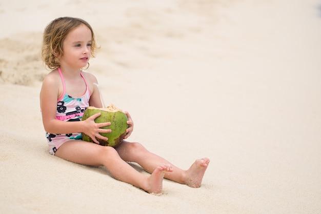 Kleines vorschulkindmädchen, das kokosnusssaft am ozeanstrand trinkt.