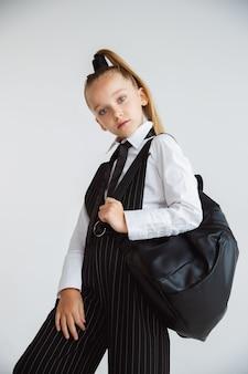 Kleines weibliches kaukasisches modell, das in der schuluniform mit rucksack auf weißem hintergrund aufwirft.