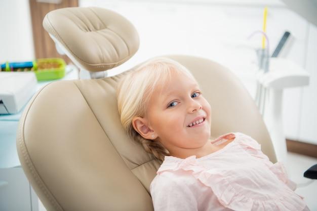 Kleines weibliches kind, das in der zahnarztpraxis sitzt