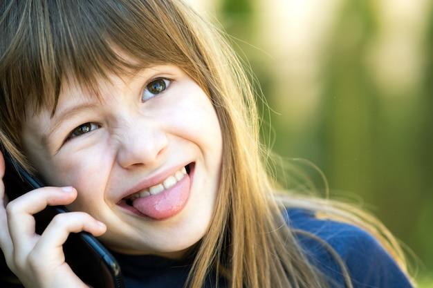 Kleines weibliches kind, das mit smartphone kommuniziert. kommunikationskonzept für kinder.
