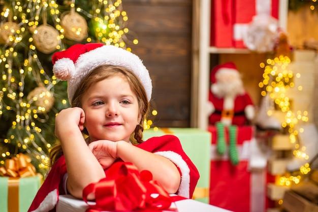 Kleines weihnachtsmann-mädchen, das geschenk macht lustiges kind, das weihnachtsgeschenk hält süßes kleines kind in der nähe von ...
