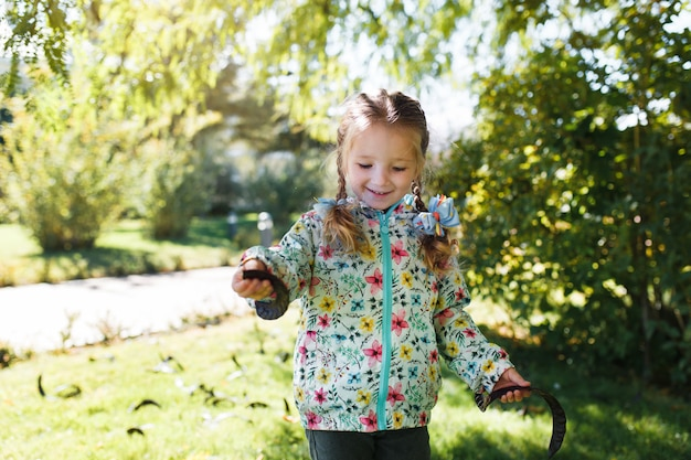 Kleines weißes glückliches mädchen mit zwei zöpfen in einer mehrfarbigen jacke hülsen von einem baum an einem warmen herbsttag erfassend
