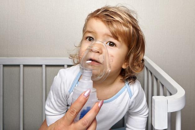 Kleines weißes mädchen ungefähr 1,5 jahre alt atmet mit vernebler, um asthmaanfall zu stoppen.