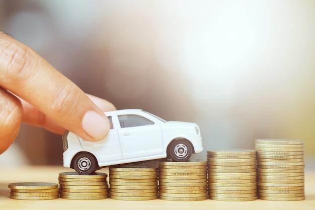 Kleines weißes spielzeugauto über viel geld gestapelte münzen. für bankdarlehen kostet finanzierung.