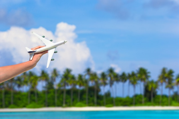 Kleines weißes spielzeugflugzeug auf tropischem strand in der menschlichen hand