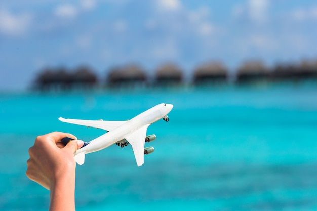 Kleines weißes spielzeugflugzeug auf tropischem strandwasserbungalow