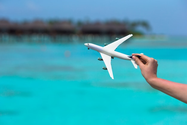 Kleines weißes spielzeugflugzeug von türkismeer