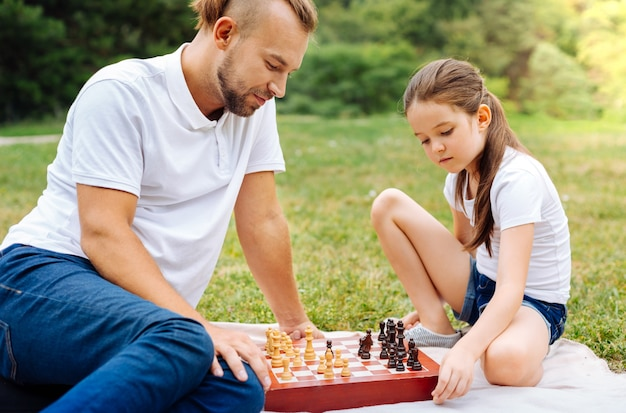 Kleines wunderkind. angenehmes kluges mädchen, das schach mit ihrem geliebten vater spielt, während sie ein picknick im park haben