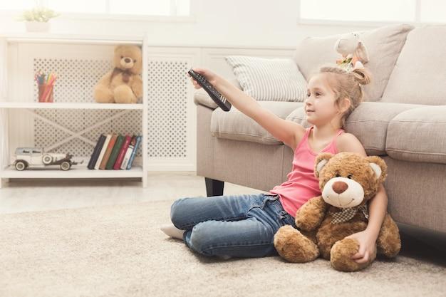 Kleines zufälliges mädchen, das zu hause fernsieht. weibliches kind, das mit ihrem spielzeugfreund teddybär auf dem bodenteppich sitzt, fernbedienung hält und kanäle umschaltet, platz kopieren