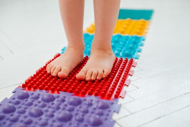 Kleinkind auf babyfußmassagematte. übungen für die beine auf orthopädischen massageteppich. vorbeugung von plattfüßen und hallux valgus