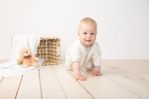 Kleinkind beim krabbeln und lächeln in die kamera mit decke, eimer und spielzeugbär auf weißem hintergrund.