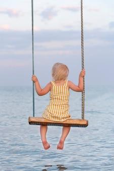 Kleinkind, das auf seil sitzt, schwingt über dem wasser. rückansicht. vertikaler rahmen. glückliche kindheit.