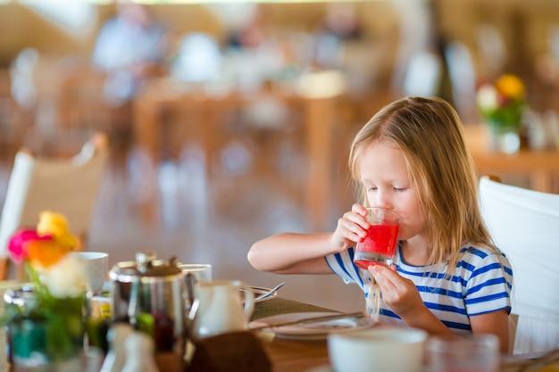 Kleinkind, das café am im freien frühstückt. entzückendes mädchen, das den frischen wassermelonensaft genießt frühstück trinkt.