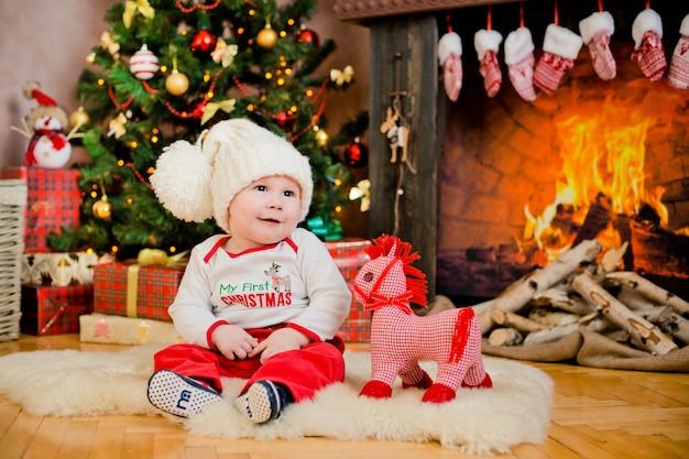 Kleinkind, das in einem weihnachtsinnenraum sitzt