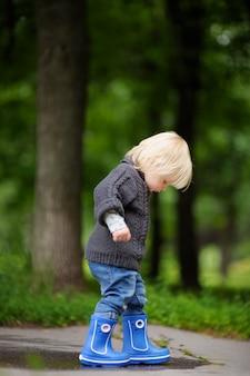 Kleinkind, das mit wasserbecken am sommer- oder herbsttag spielt