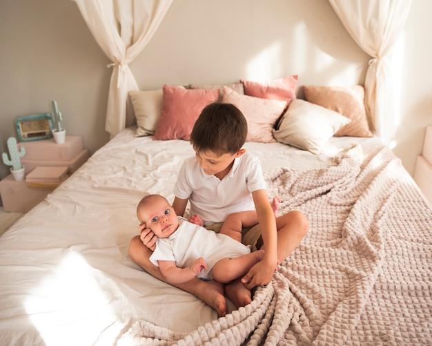 Kleinkind, das neugeborenes baby umarmt