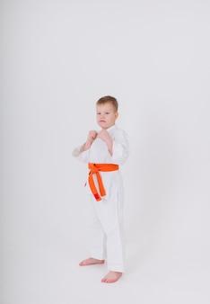 Kleinkind ein junge in einem weißen kimono mit einem orangefarbenen gürtel steht in einer pose auf einer weißen wand