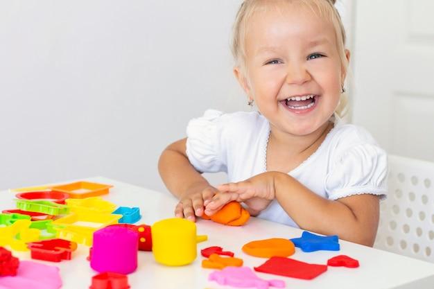 Kleinkind formt aus farbigem plastilin auf einem weißen tisch. die hand eines kleinen kindes drückt farbige plastilinstücke zusammen. kreativität der kinder, lernspiele, feinmotorik
