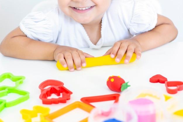 Kleinkind formt aus farbigem plastilin auf einem weißen tisch
