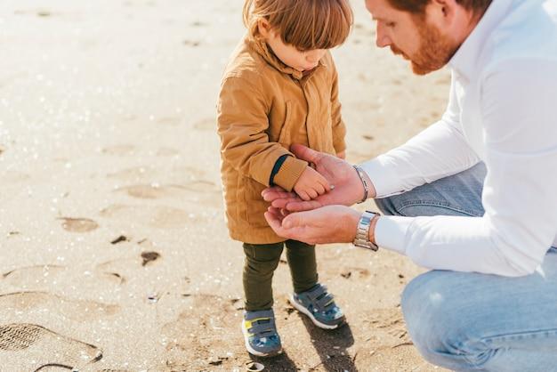 Kleinkind im mantel, der mit vati spielt