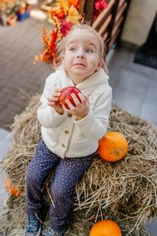 Kleinkind in der weißen strickjacke, die auf dem heuschober mit kürbisen am portal sitzt und mit apfel spielt.