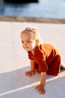 Kleinkind in einem terrakotta-kleid kriecht auf einem bootsanleger am meer.