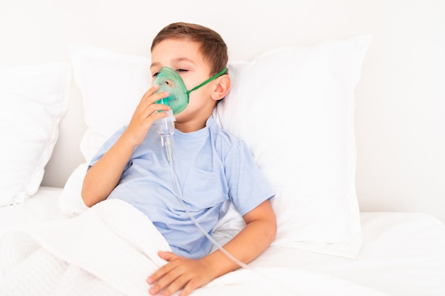 Kleinkind junge liegt krank mit einer maske zum einatmen im bett