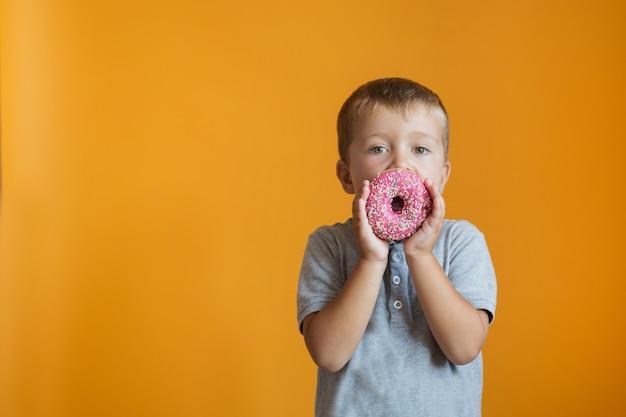 Kleinkind junge mit donat in der nähe seines mundes