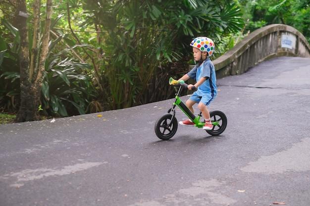 Kleinkind jungen kind trägt schutzhelm reiten balance fahrrad einen hügel hinunter