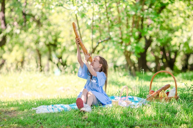 Kleinkind mit großem brot auf picknick im park