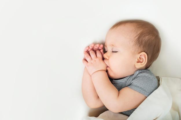 Kleinkind schläft mit finger im mund auf bettnahaufnahme gesundes babyschlafkonzept und kopierraum