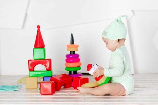Kleinkind spielt mit bunten würfeln im kinderzimmer zu hause, das konzept der entwicklung und freizeit von kleinkindern