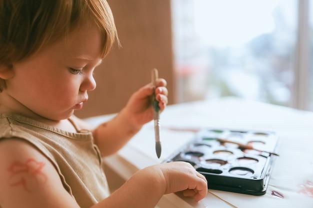 Kleinkind zu hause malt farben auf sich selbst nahaufnahme
