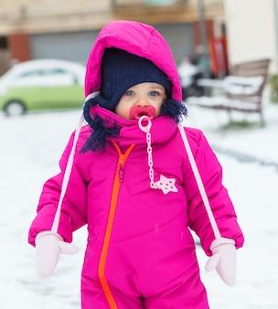 Kleinkindbaby in einer magentaroten schneeklage, die auf dem schnee spielt.