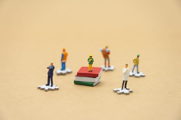 Kleinkinder miniaturleute, die auf büchern stehen