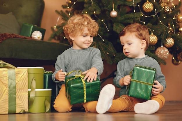Kleinkinder nähern sich weihnachtsbaum in einer grauen strickjacke
