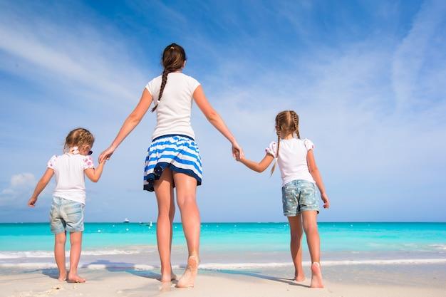 Kleinkinder und glückliche mutter während der strandferien