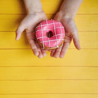 Kleinkinderhände, die süßen donutnachtisch halten.