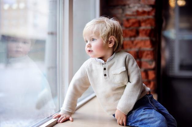 Kleinkindjunge, der auf dem fensterbrett sitzt und das panoramische fenster betrachtet