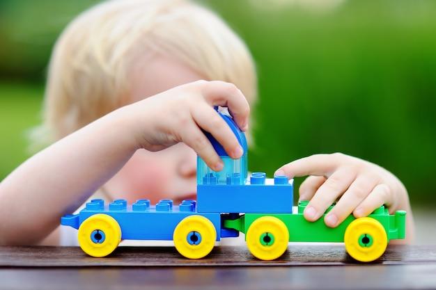 Kleinkindjunge, der draußen mit spielzeugzug am warmen sommertag spielt. spielzeug für kleine kinder